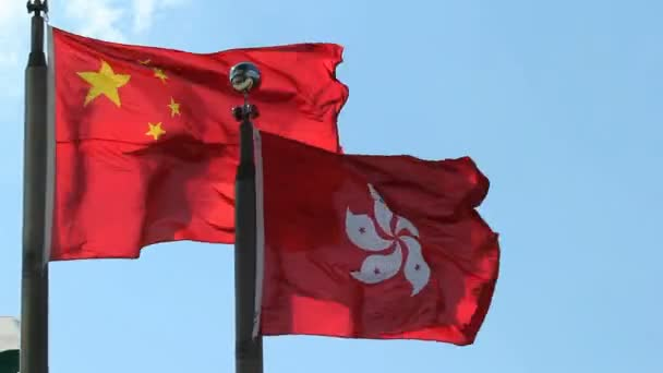 Hong Kong and Peoples Republic of China Flags flying side by side against clear blue sky on a windy day 1080p