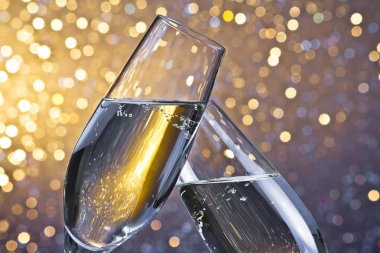 champagne flutes with golden bubbles on light bokeh background