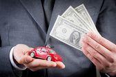 autíčko a dolary v rukou obchodní muž koncept pro pojištění, nákup, pronájem, paliva nebo služby a nákladů na opravy
