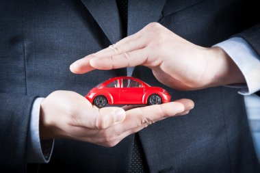 businessman protect with his hands a red car, concept for insurance, buying, renting, fuel or service and repair costs