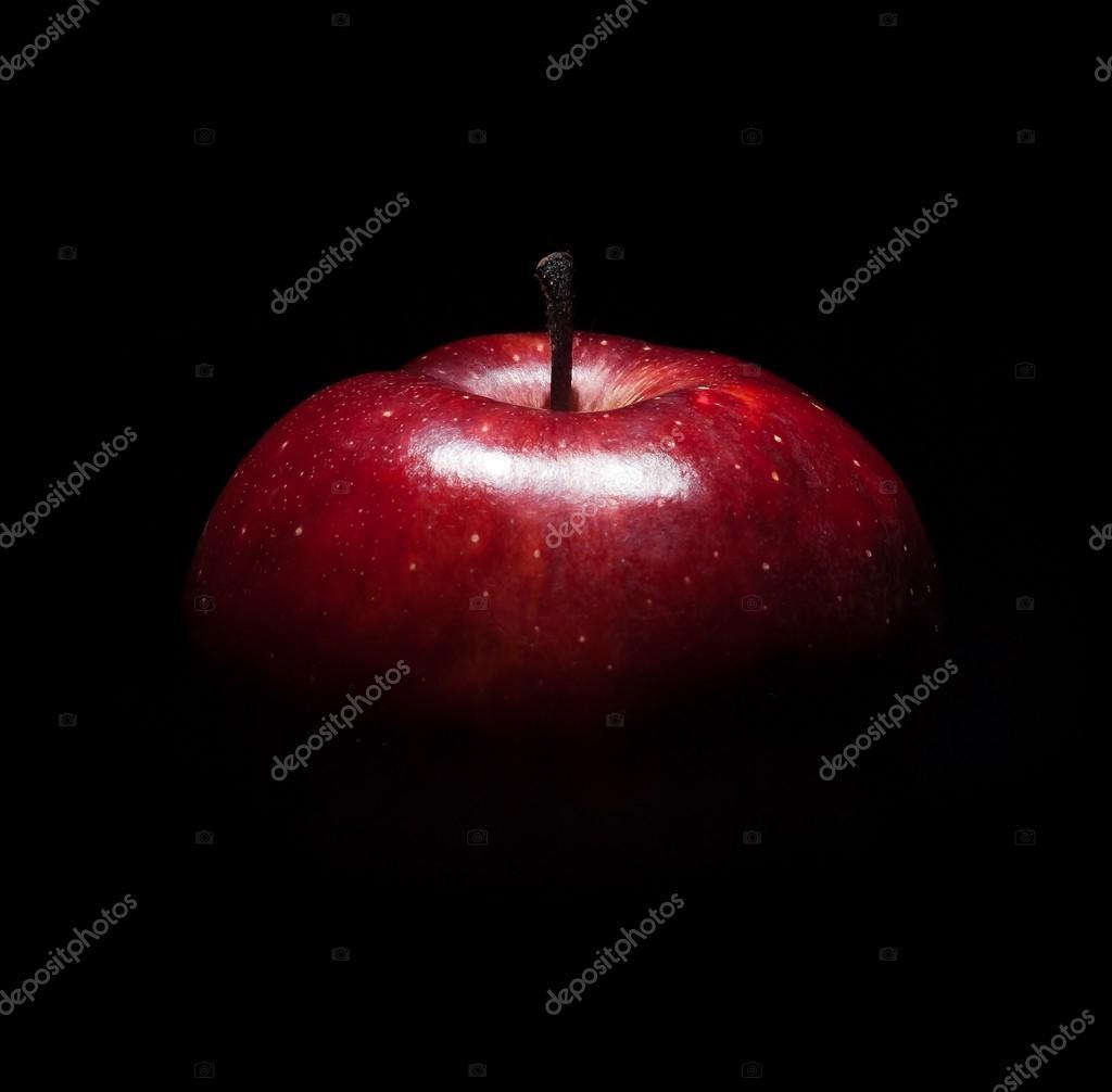 fresh red apple against black background