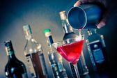 Barman červený koktejl nalil do sklenice s ledem