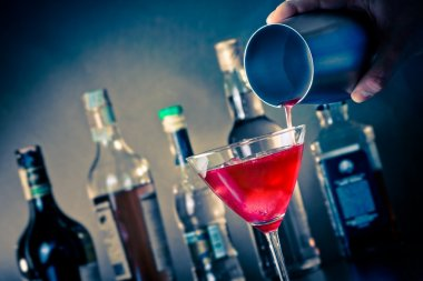 Barman pouring a red cocktail into a glass with ice on blue light disco atmosphere stock vector