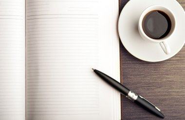 Open a blank white notebook, pen and coffee on the desk