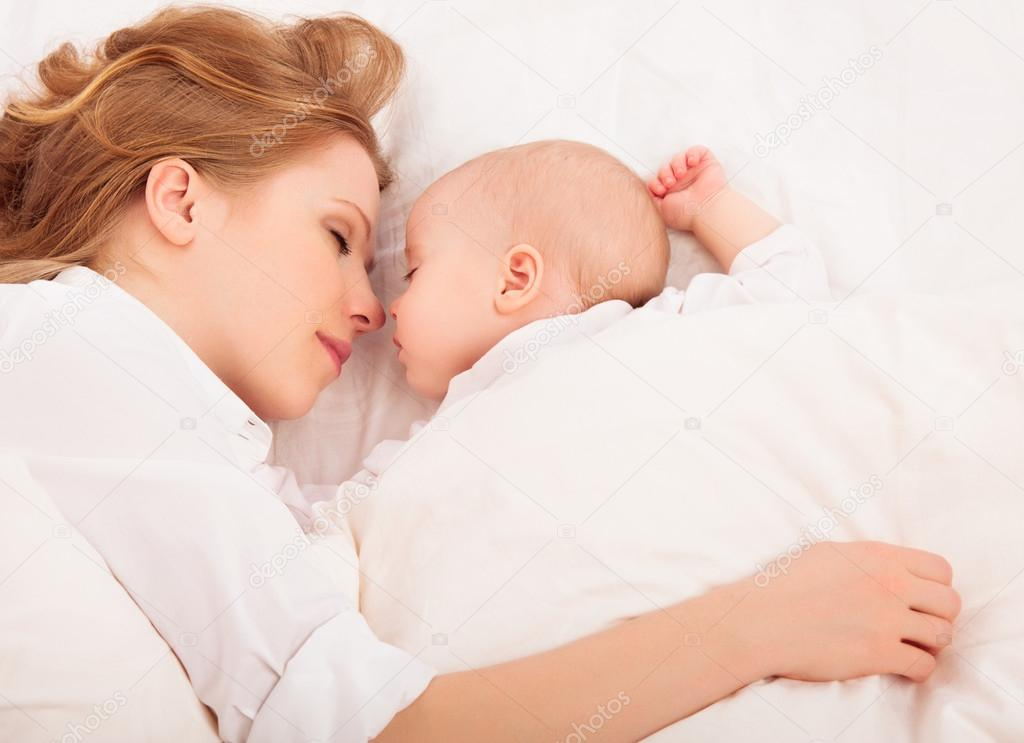 Mother embraces the newborn baby sleeping together in bed stock photo
