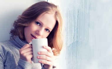 Beautiful dreamy young woman with a cup of hot drink coffee at the window in the rain stock vector