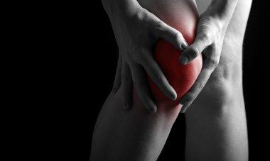 pain in the knee. Chiropractor doing massage in sick knee in red