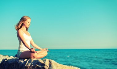 woman meditating in lotus yoga on beach
