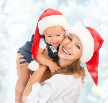 Happy family mother and baby in Christmas hats