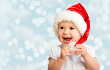 Beautiful funny baby in a Christmas hat on blue
