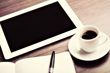 workplace, office desk: coffee and tablet pc and notebook with p