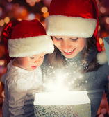 Weihnachten magische Geschenk-Box und eine glückliche Familie Mutter und baby
