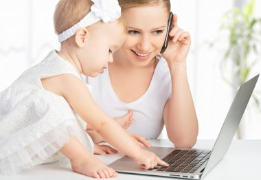 mother with baby daughter works with a computer and phone