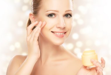 young beautiful woman using a face cream
