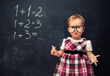 baby girl  in glasses and chalk at a school board with arithmeti