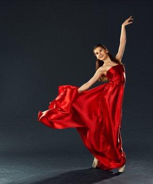 Beautiful ballerina dancing a long red dress flying