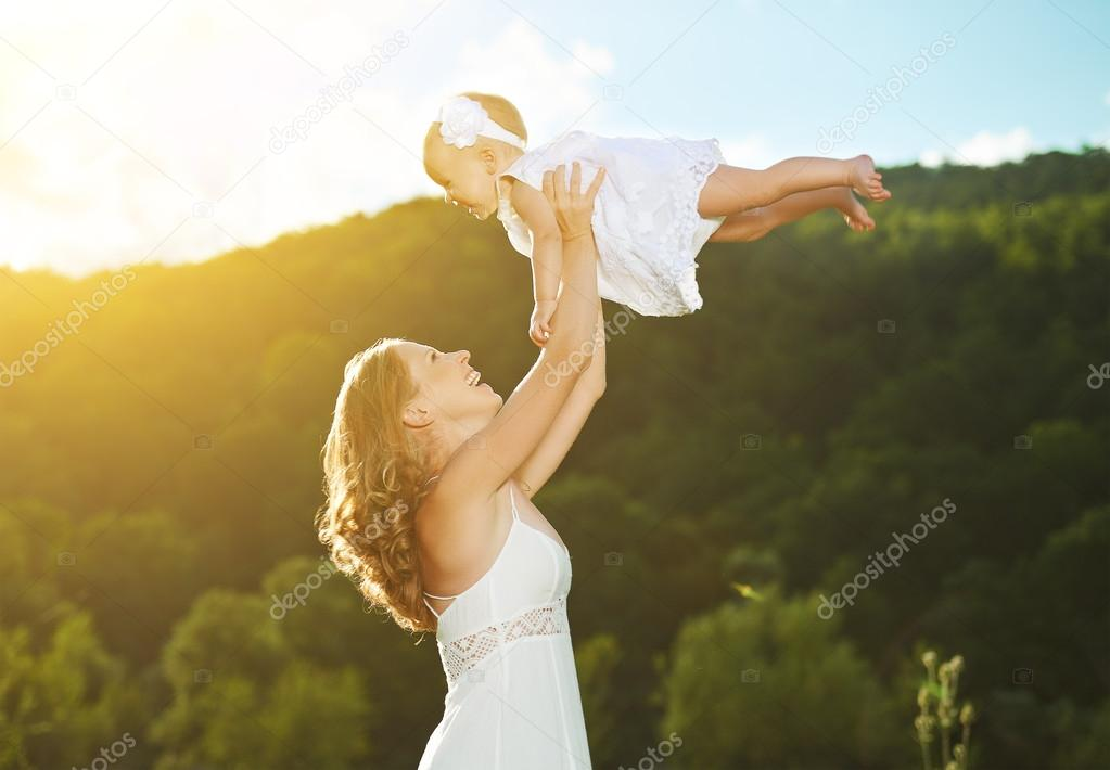 happy family. Mother throws up baby in the sky
