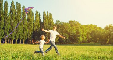 Dad and son child flying a kite in summer nature