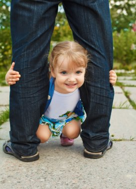Little girl holding the feet of parents