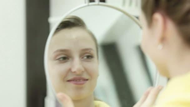 A lány, miután egy haj-vágás nézi magát a tükörben