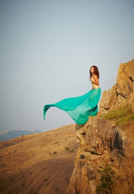 A girl stands on the edge of a cliff.