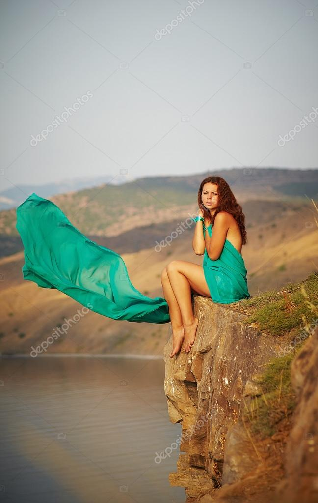Girl sitting on the edge of a cliff