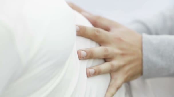 Hands stroking pregnant belly