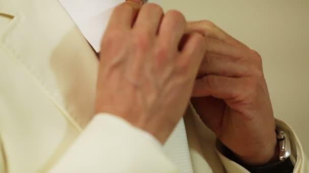 Vőlegény szigorítja a nyakkendő. Násznagy segít neki, és javítja a sál