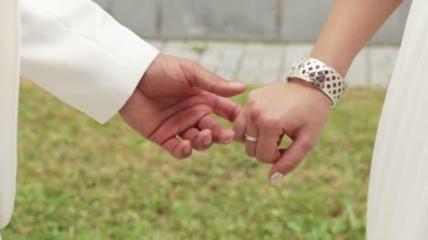 nevěsta a ženich, drželi se za ruce. nevěsta má Kytice svatební.