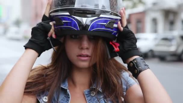 Beautiful girl takes a motorcycle helmet and smiling