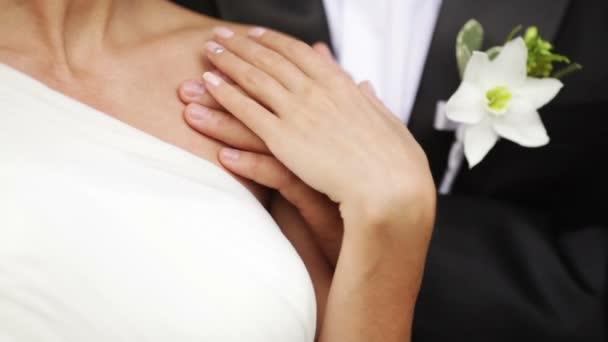 pár kéz mellett található a gyönyörű esküvő boutonniere