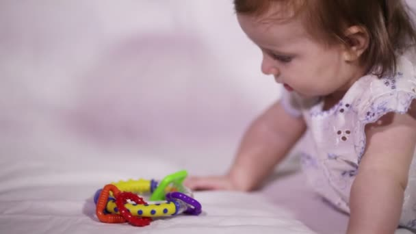 Mommy gives the child a colorful baby rattle