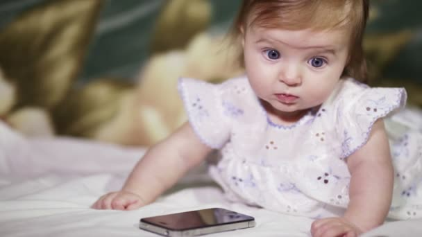 Infant girl listening to a mobile phone