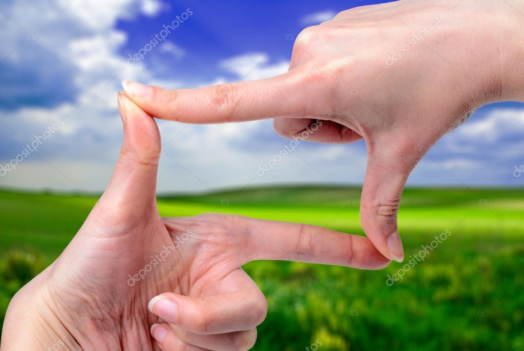 Hands framing a landscape