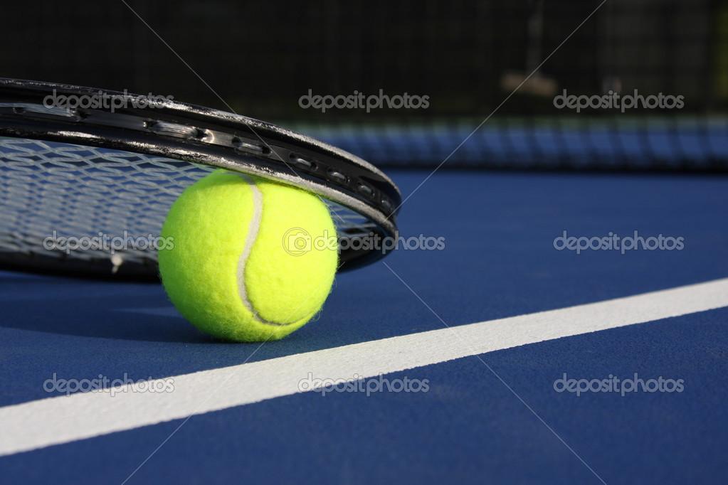 Balle de tennis et de la raquette sur un court bleu