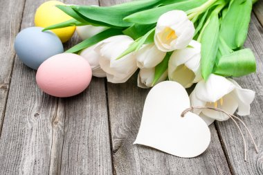 Easter eggs and tulips with a tag on wooden background stock vector