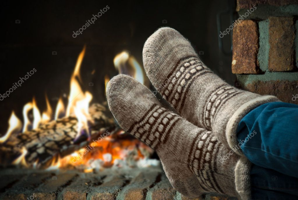 Feet in wool socks warming at the fireplace