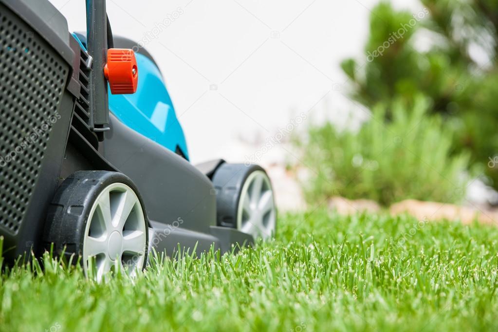 Lawn mower on a green meadow