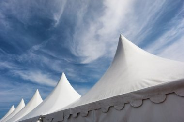 Row of white event and party tents against blue sky
