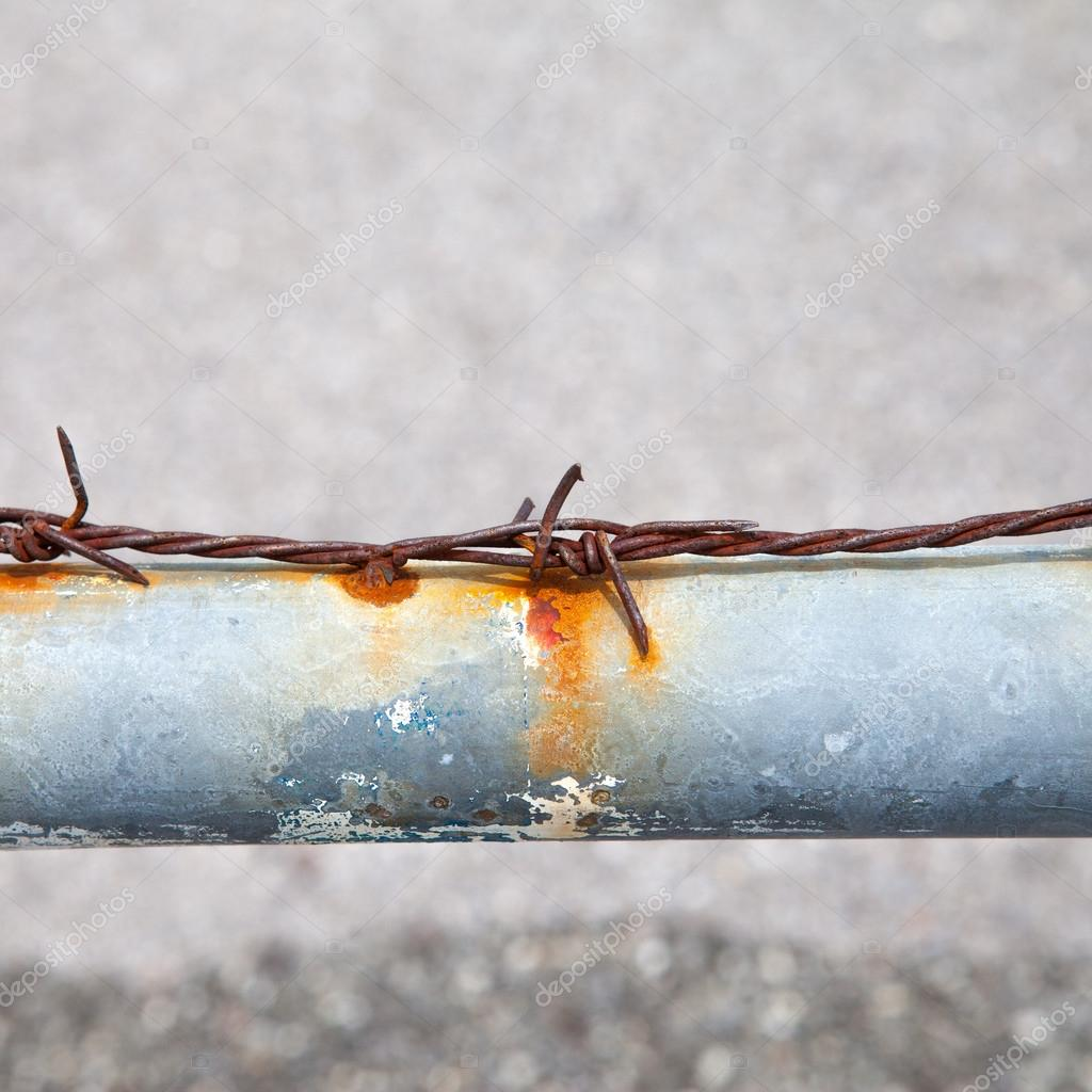 Rusty barbed wire on a metal tube — Stock Photo © pinkblue #26142873