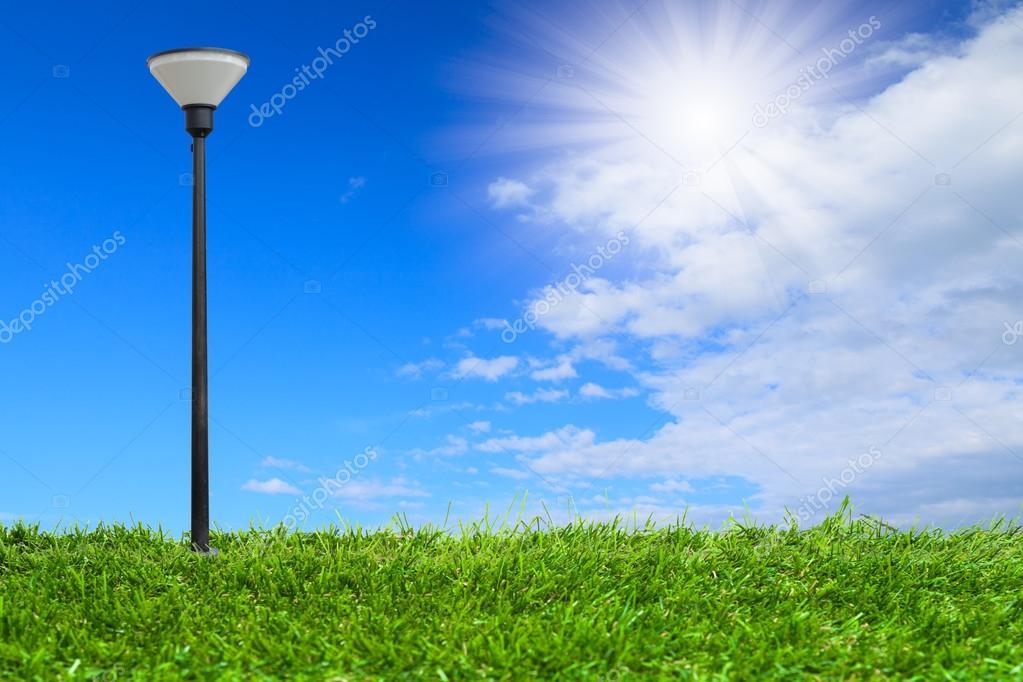Streetlamp on artificial grass under blue sky