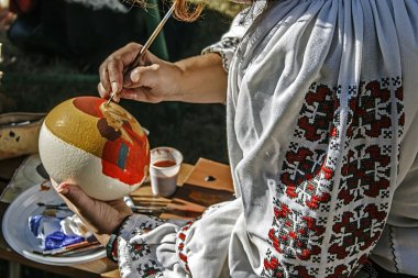 Woman painting ostrich egg