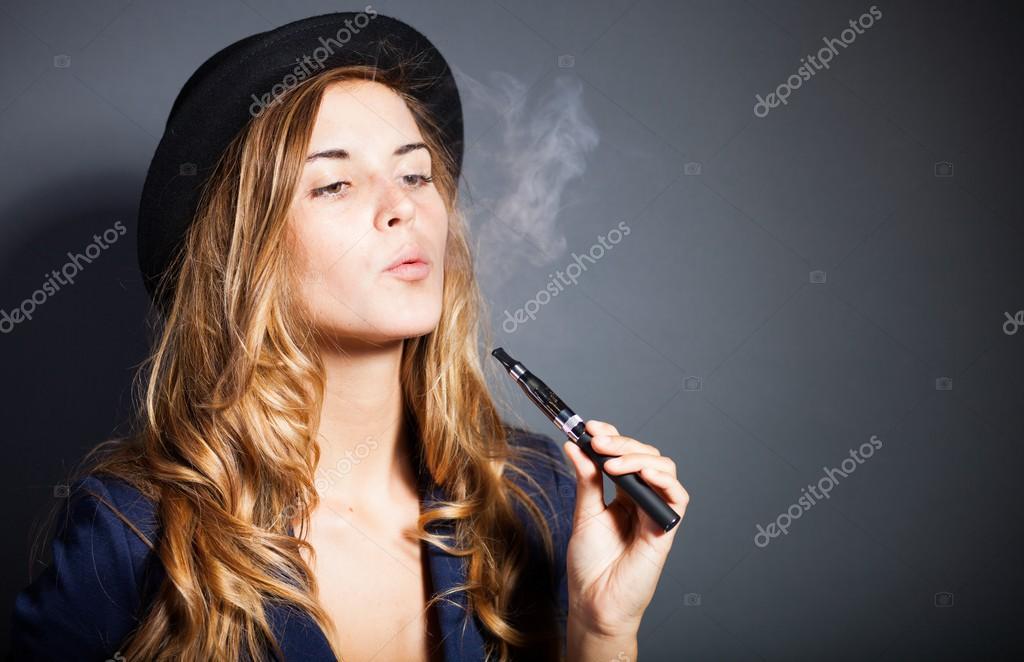 d9ba21170e551 Elegante mujer fumando cigarrillo electrónico con humo vistiendo traje y  sombrero — Fotos de Stock