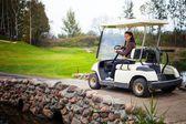 Mladá žena hnací golfový vozík