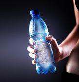 Fotografia bottiglia dacqua in mano donna fitness, concetto di salute