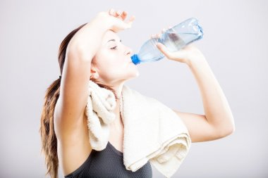 Attractive woman drinking water after exercise