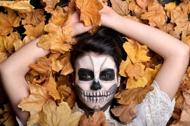 Girl with painting dead mask skull with leaves