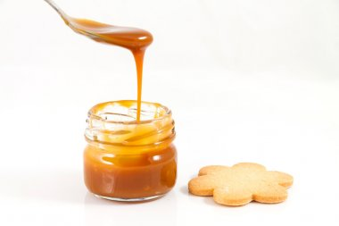 Pouring caramel in a small jar with a spoon with a cookie next t