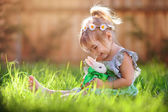 Fotografie Cute little girl with a bunny rabbit has a easter at green grass