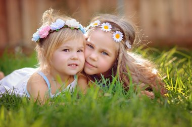 portrait of two happy little sisters on green grass